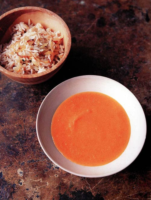 A white bowl of orange carrot and lentil soup with a bowl of rice nearby