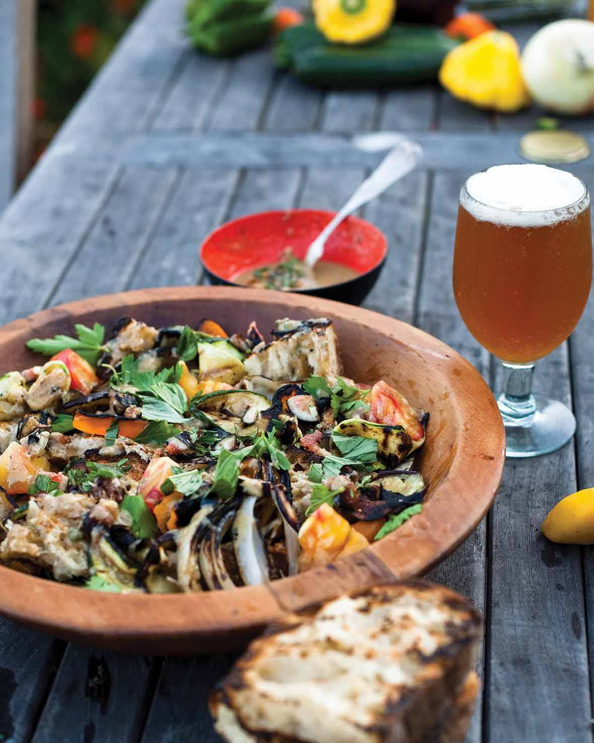 A wooden bowl filled with Escalivada bread salad and a frothy beer on the side.