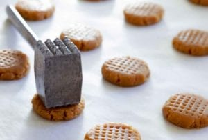 Unbaked crisp peanut butter cookies on a baking sheet being hammered to create cross hatch marks.