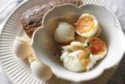 Halved soft-boiled eggs and toast on a plate with egg shells.