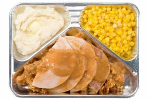 A tv dinner with sliced meat, stuffing, gravy, corn, and mashed potatoes in a foil container.