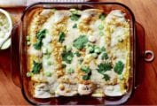 A glass baking dish with four chicken enchiladas topped with cheese, sliced scallions, and cilantro leaves.