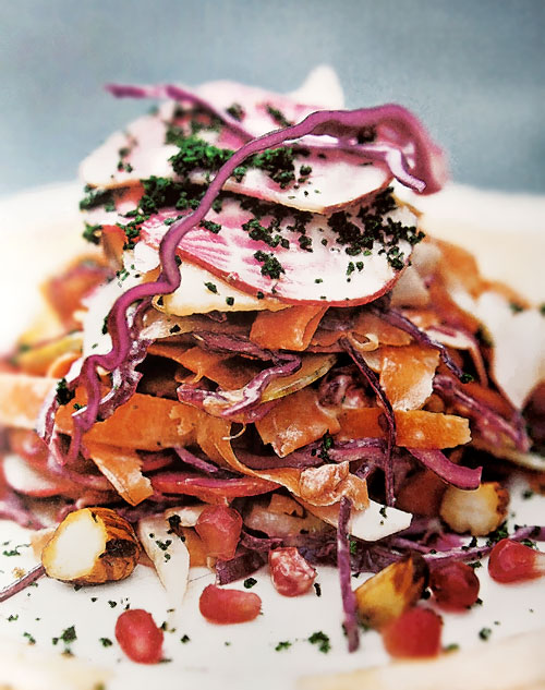 A pile of autumn coleslaw with apples, hazelnuts, red cabbage, beets, and pomegranate seeds