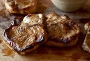 Four juicy seared maple-brined pork chops with pear chutney on a cutting board