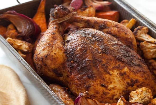 A deep roasting pan filled with roast chicken and vegetables