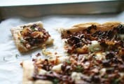 A sheet pan with n onion thyme tart on it, covered with cooked onions, thyme on a puff pastry crust