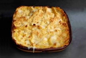 A cooked pumpkin lasagne in a square casserole dish.