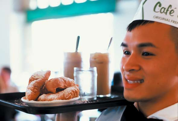 A person carrying a tray with a plate of beignets, two milkshakes, and a glass of water.