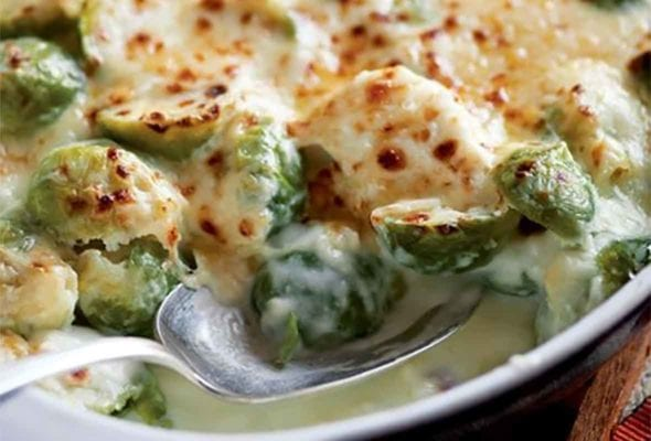 A white gratin dish filled with creamy Brussels sprouts and covered in cheese