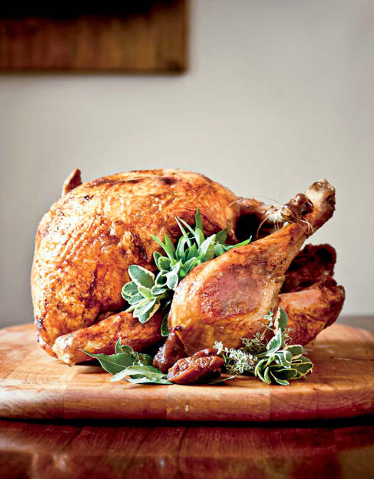 A whole deep-fried turkey, garnished with sage, bay, and thyme leaves on a wooden cutting board.