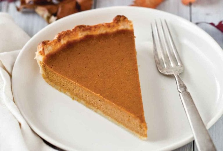 A slice of drunken pumpkin bourbon tart on a white plate with a fork beside it and a mini pumpkin and leaves in the background.