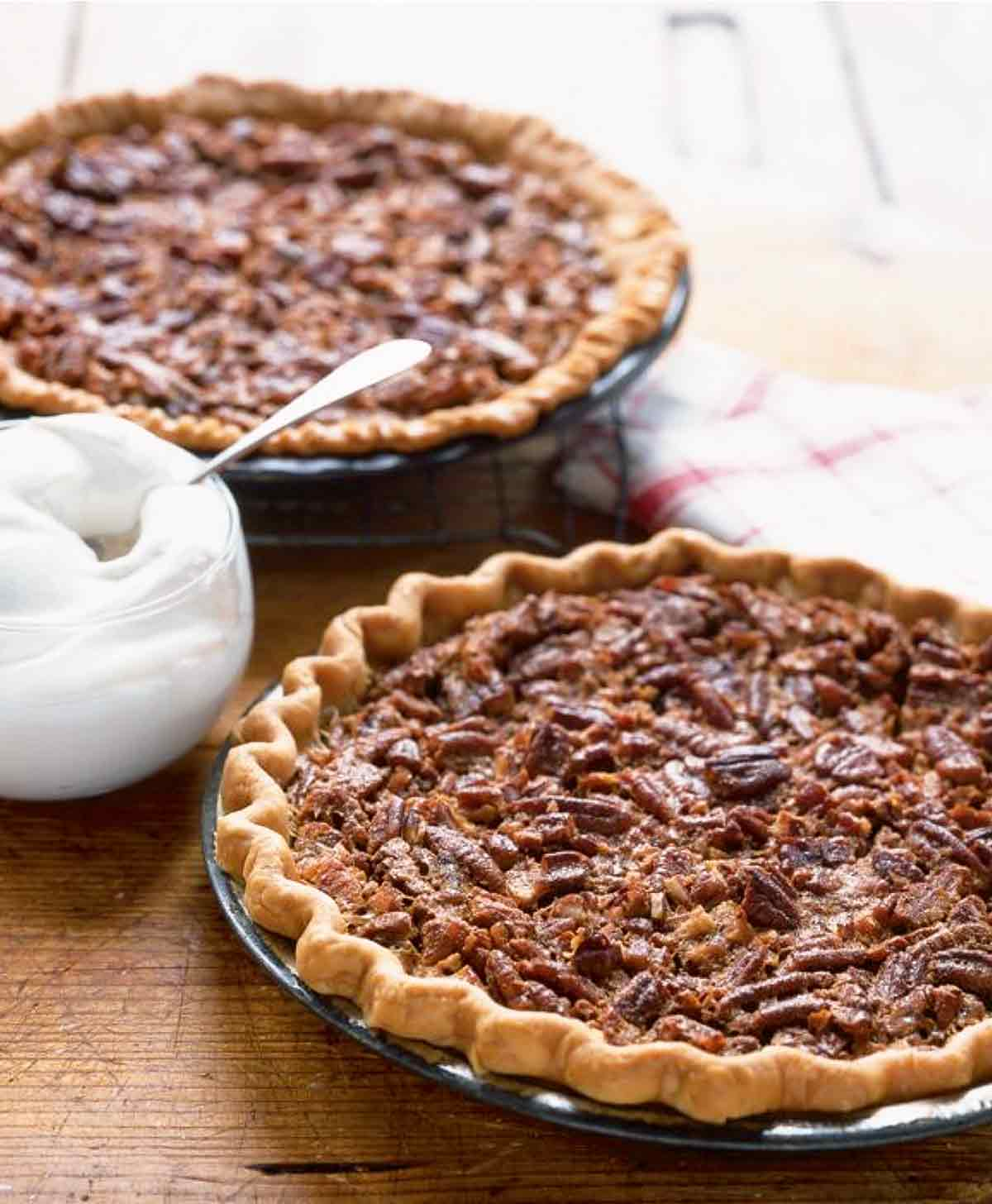 Two Southern pecan pies in pie plates with a bowl of whipped cream in between them.