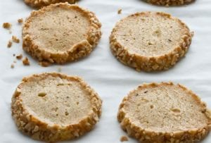 Four delicate Stilton Walnut crackers, edges rolled in chopped walnuts, on a parchment-lined sheet pan