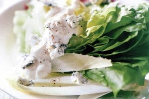 A Bibb wedge, radicchio, endive, and blue cheese dressing on a white plate set on top of blue and yellow linens.