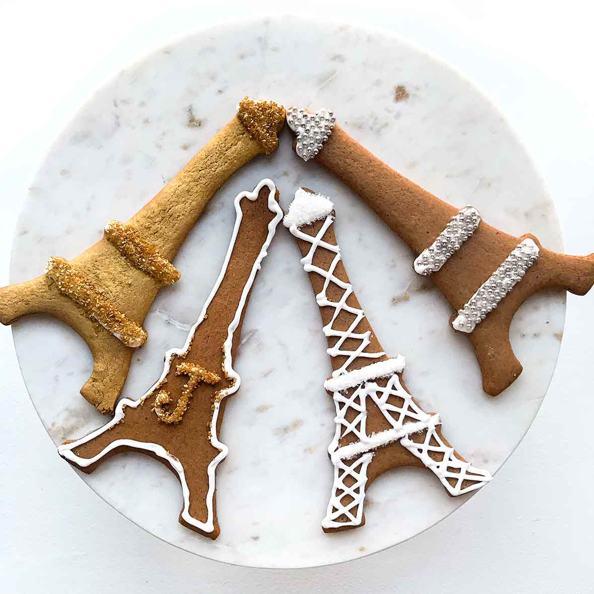 Four Swedish black pepper cookies called pepperkakor cut into Eiffel Tower shapes and decorated