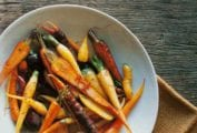 A white bowl of braised saffron carrots on a piece of burlap on a wooden table.