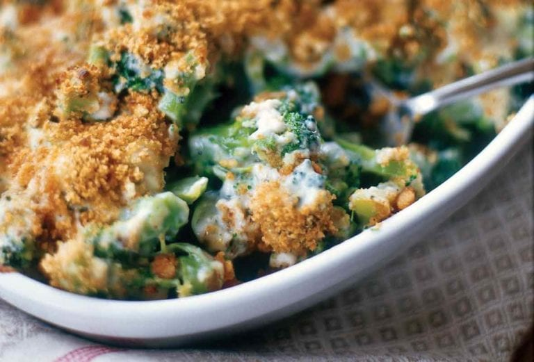 A white gratin dish filled with cheesy broccoli and topped with toasted breadcrumbs