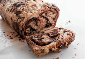 A loaf of chocolate babka on a sheet of parchment with one slice cut off.