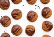 A dozen mounded molasses cookies, half of each is covered in chocolate on a white background