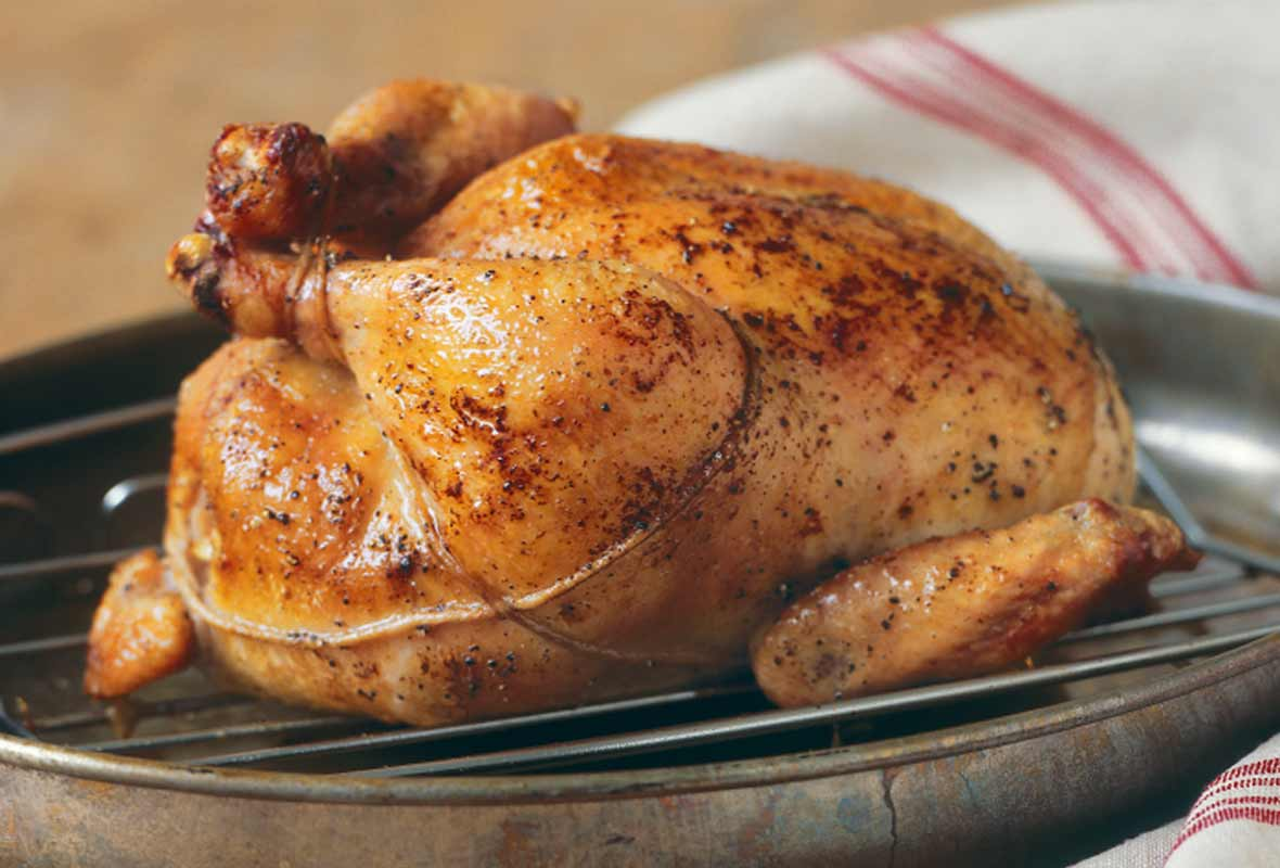 A trussed classic roast chicken on a rack, set inside a skillet.