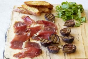 Slices of duck prosciutto, halved grilled figs, arugula, and a few crostini on a wooden serving board.