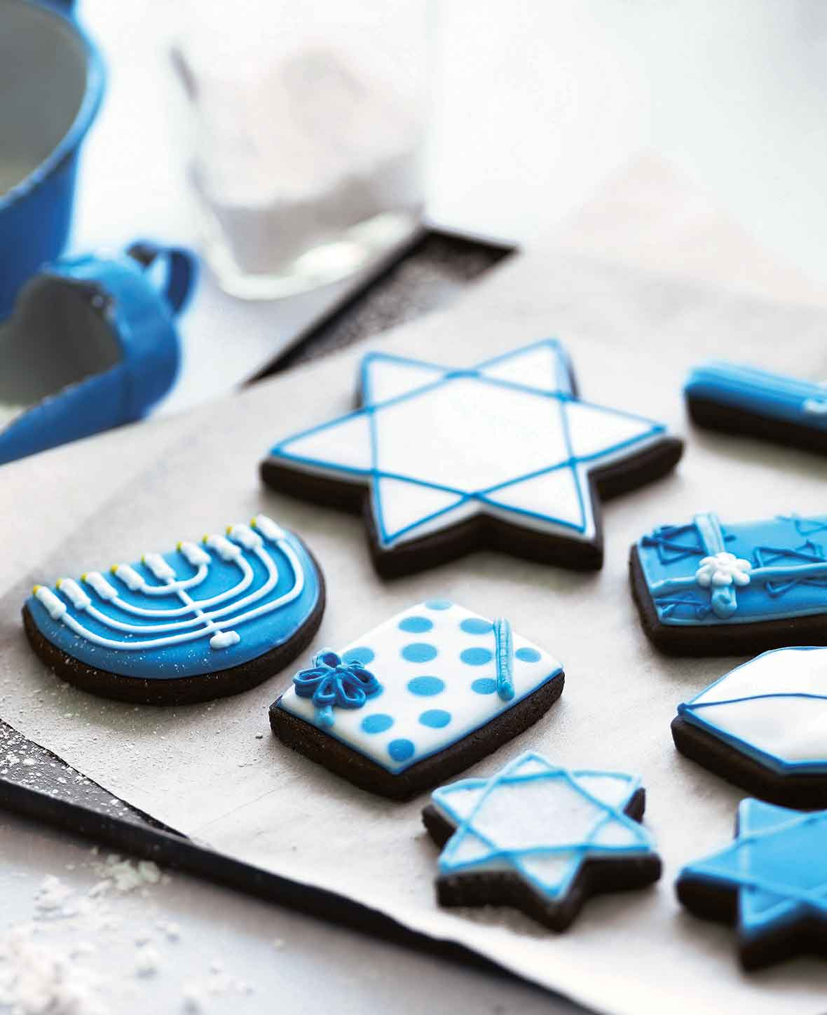 A selection of frosted cookies decorated for Hanukkah, on a parchment-lined cookie sheet