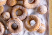An assortment of round doughnuts and doughnut holes coated with sugar piled on a sugar-coated baking sheet