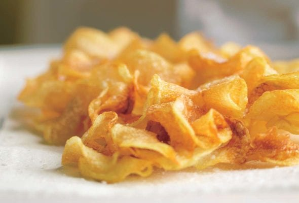 A pile of homemade potato ruffles on a white surface.
