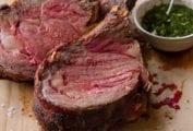 Three slice of medium rare standing rib roast au jus on a cutting board