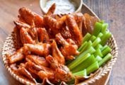 A basket of broiled buffalo wings with celery sticks and blue cheese dressing.
