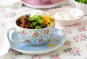 A pretty saucer and teacup filled with game day chili, and topped with scallions, Cheddar, and sour cream.