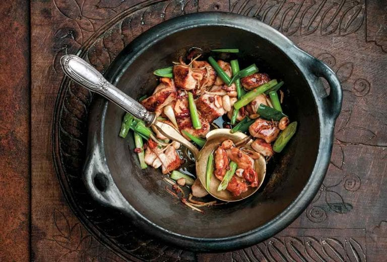 Black pottery bowl filled with the Chinese dish gung bao chicken