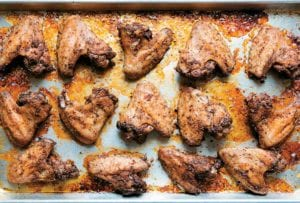 A rimmed baking sheet filled with peppery chicken wings