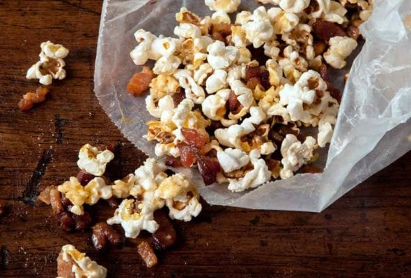 Open waxed paper bag with popcorn and maple bacon bits spilling out