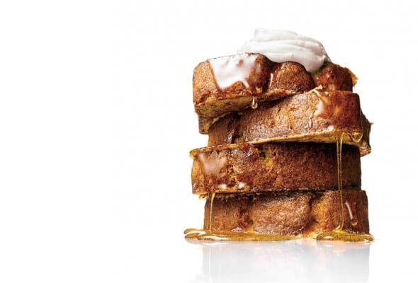 A stack of four slices of banana bread French toast dripping with maple syrup and topped with whipped cream