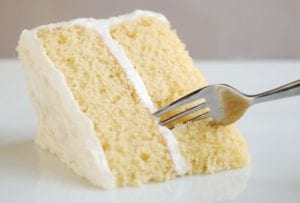 A wedge of classic white cake and white frosting with a fork cutting in
