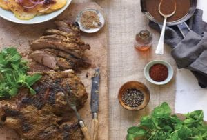 A partially carved leg of lamb with Moroccan spices on a wooden board with small dishes of spices, oil, and pan sauce beside it.