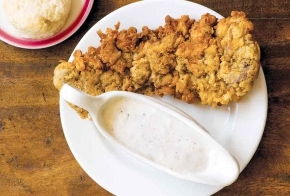 A piece of chicken fried steak with a dish of cream gravy beside it all on a white plate.