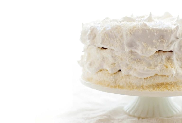 A 3-layer coconut angel food cake covered in white frosting on a white cake stand