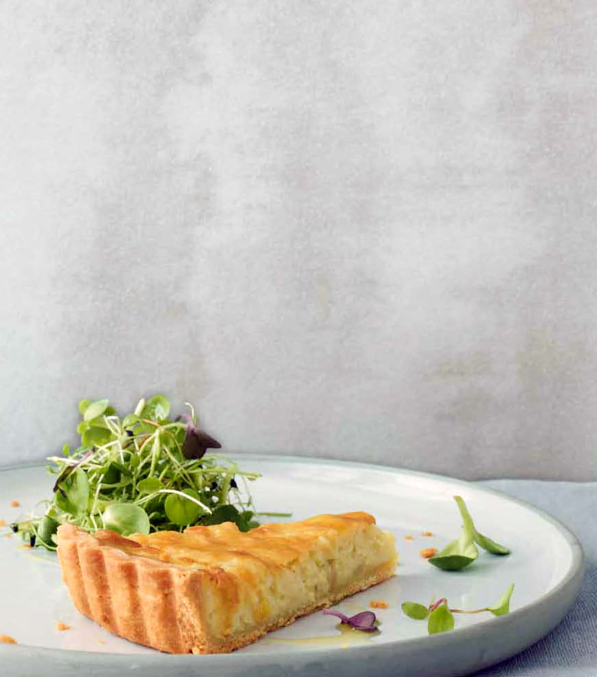 A slice of a creamy onion tart, with a flaky crust and tossed mixed salad on a white plate