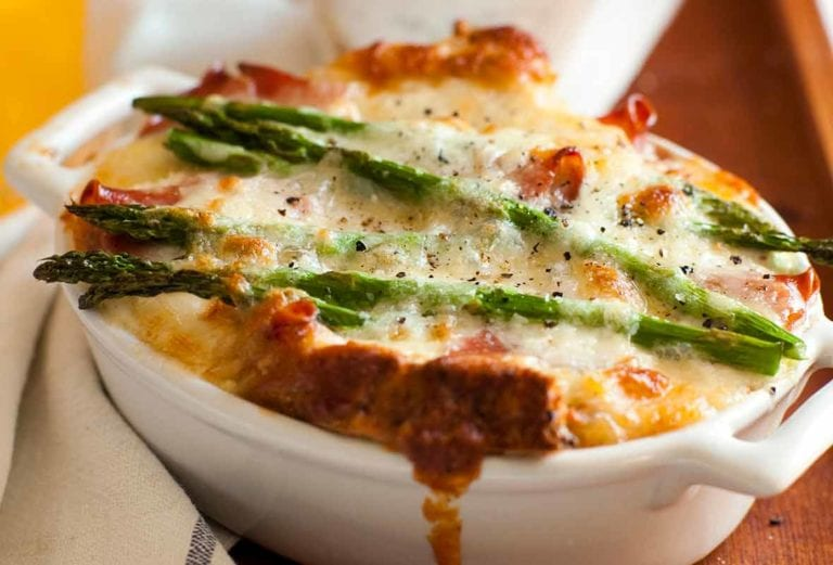 A white oval casserole filled with asparagus, egg and cheese strata--bread, Fontina cheese, eggs, prosciutto, and asparagus