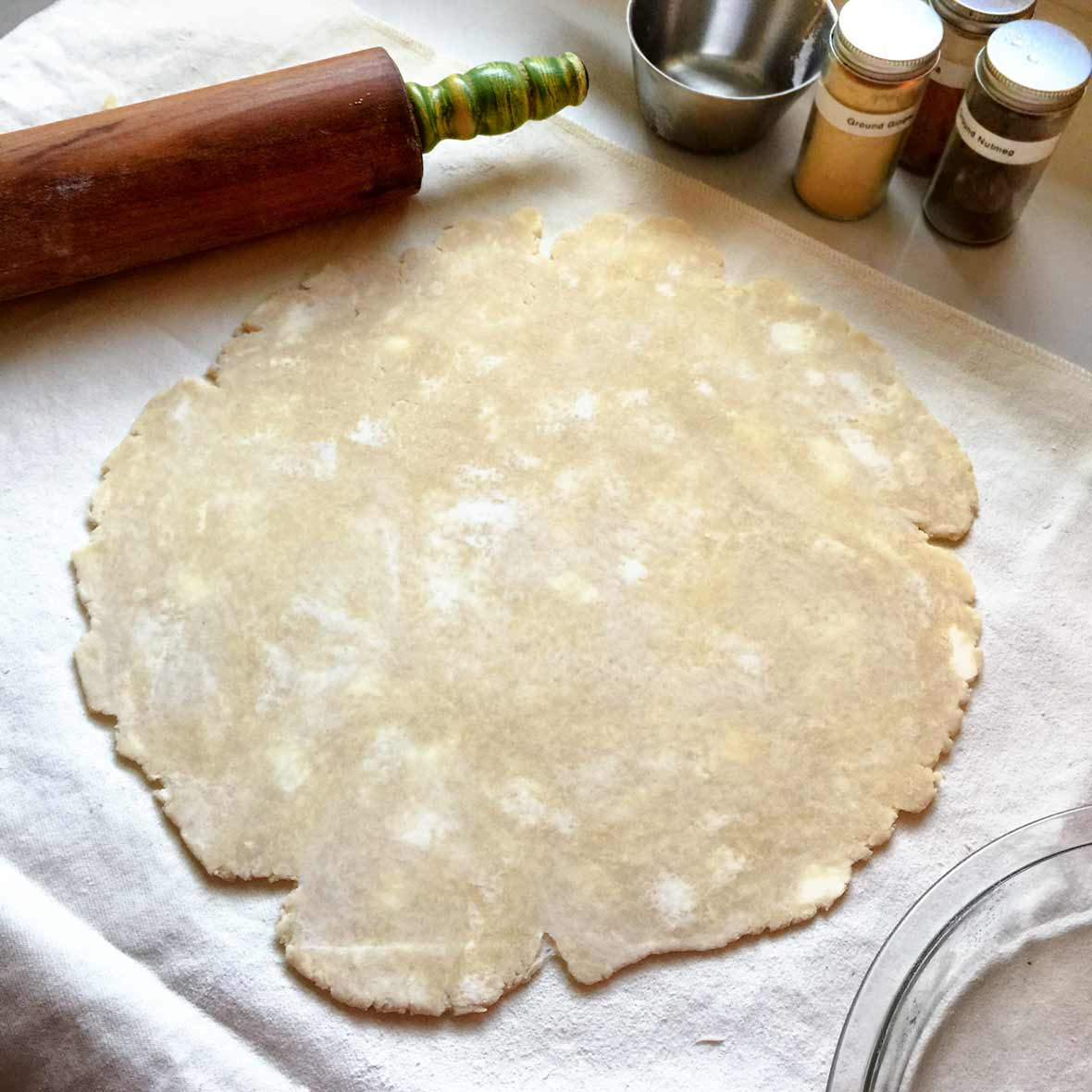 An uncooked pie crust rolled out on a floured surface with a rolling pin alongside