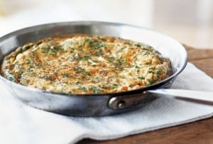 A frittata with leeks and herbs in a metal skillet on a white linen mat.