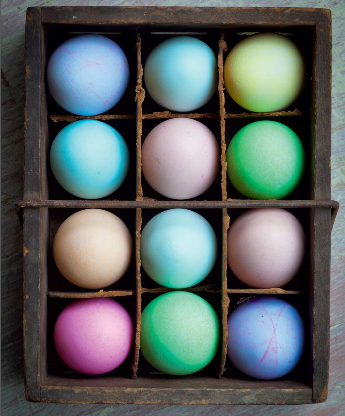 A crate filled with an assortment of dyed easter eggs.