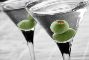 Two classic martinis, each garnished with two green olives.