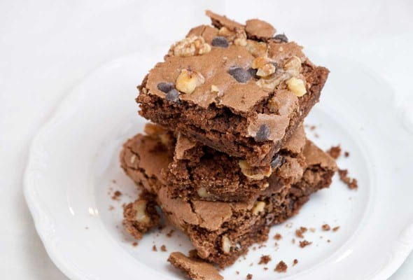 Three Passover brownies stacked on top of each other on a white plate.