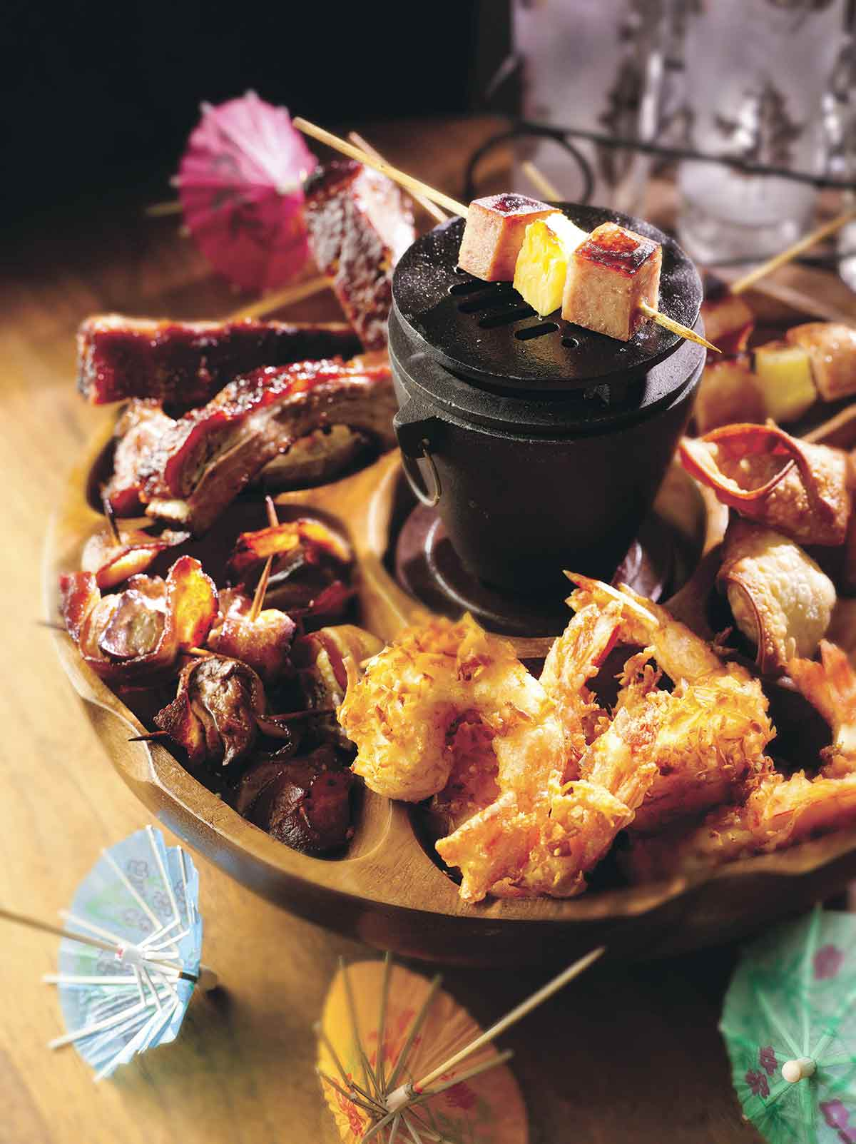 A wooden pupu platter filled with coconut shrimp, spam and pineapple skewers, and ribs.