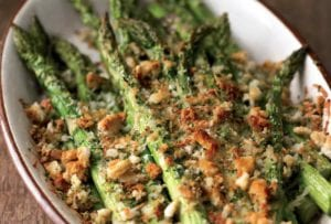 Oval casserole dish with spring asparagus and Asiago gratin, topped with coarse bread crumbs