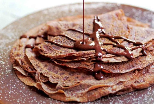 A stack of Tom Aikens' chocolate crepes being drizzled with chocolate sauce.