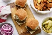 Three lamb burgers with chunky potato wedges and sliced pickles in separate bowls.